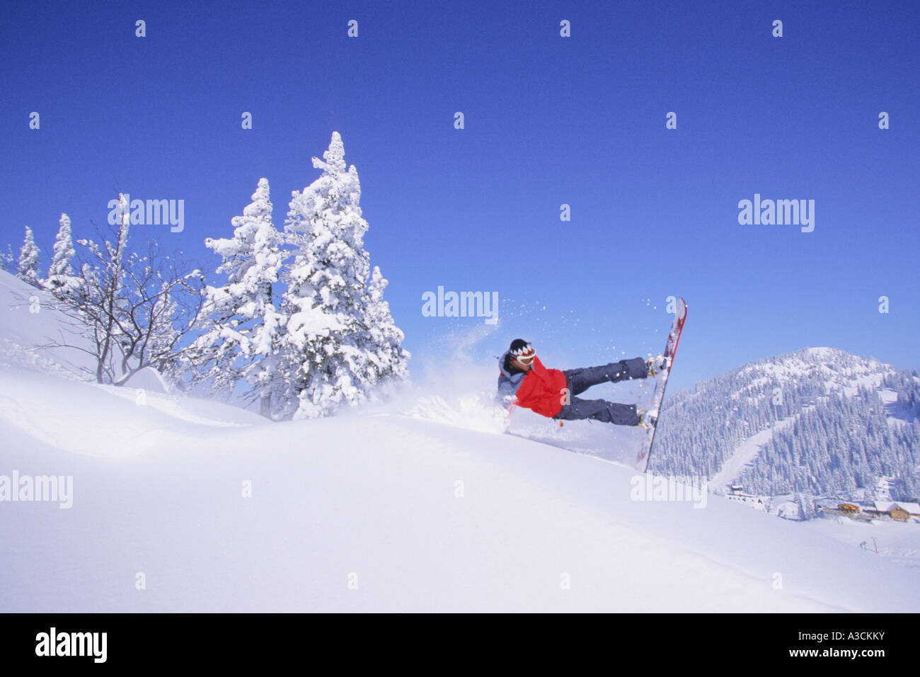 snowboarder jumping downhill, Austria, Alps - Stock Image