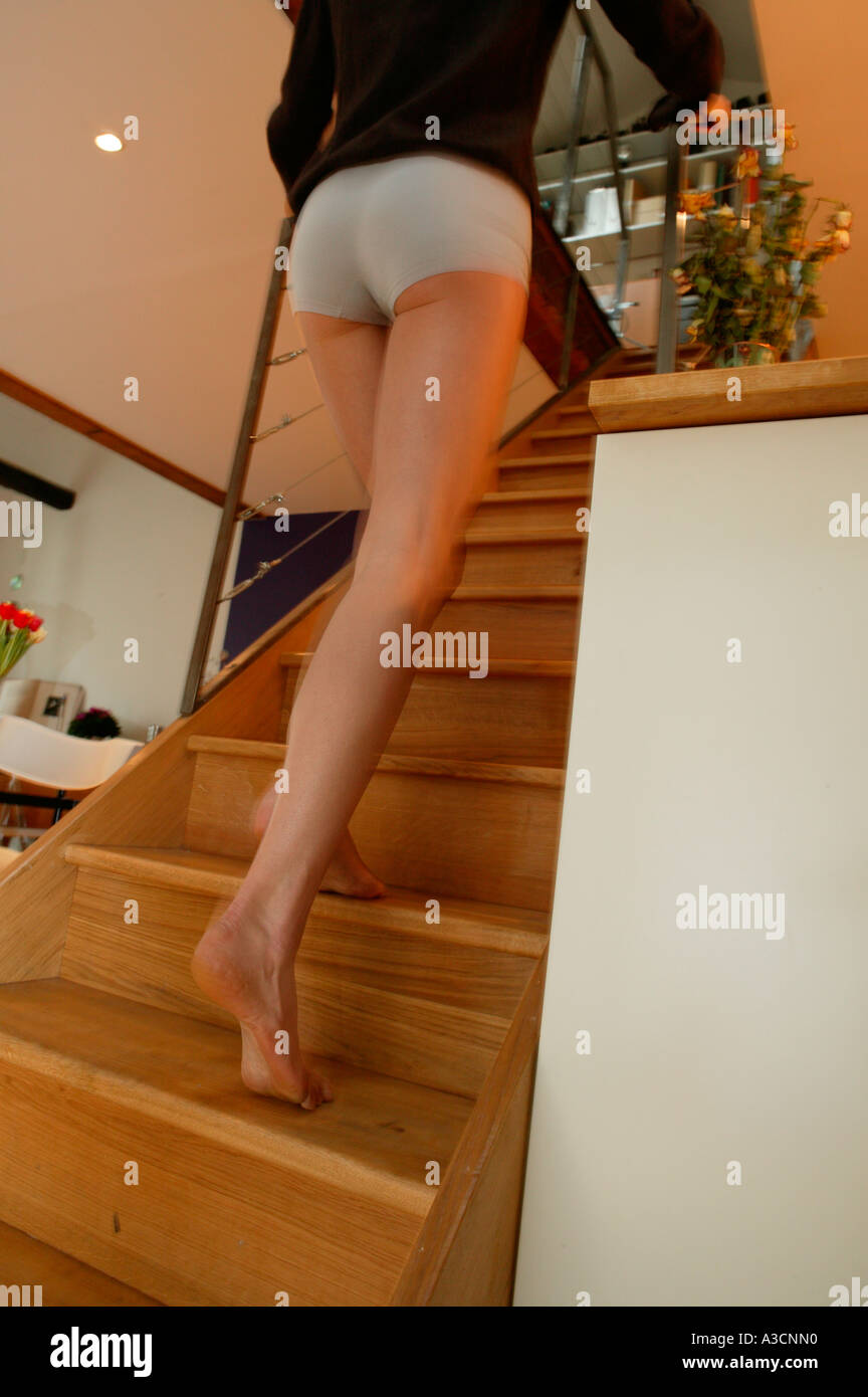 Young woman in knickers going upstairs, rear view - Stock Image