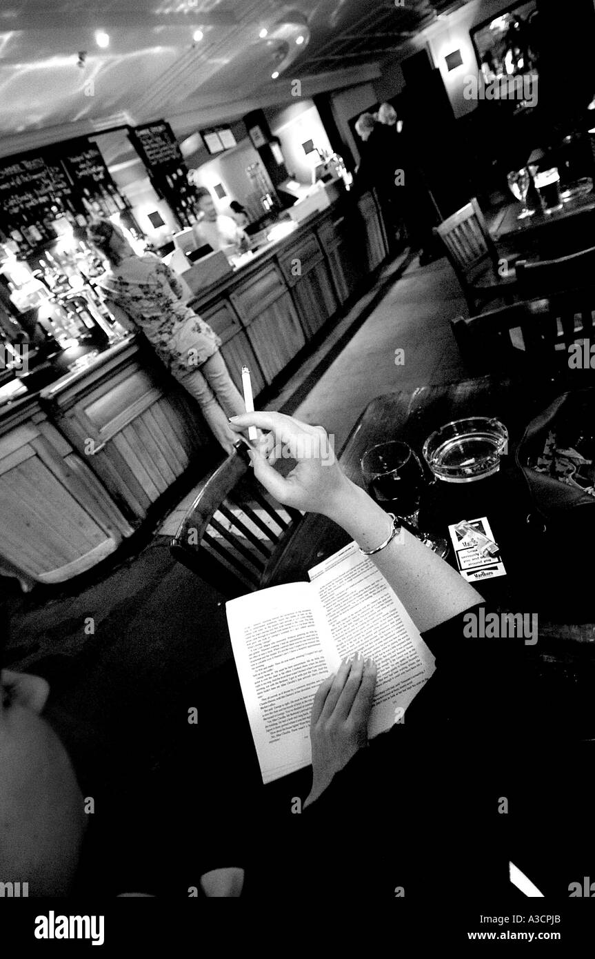 A lady reads a book and smokes in The Falcon Pub Clapham North London United Kingdom - Stock Image
