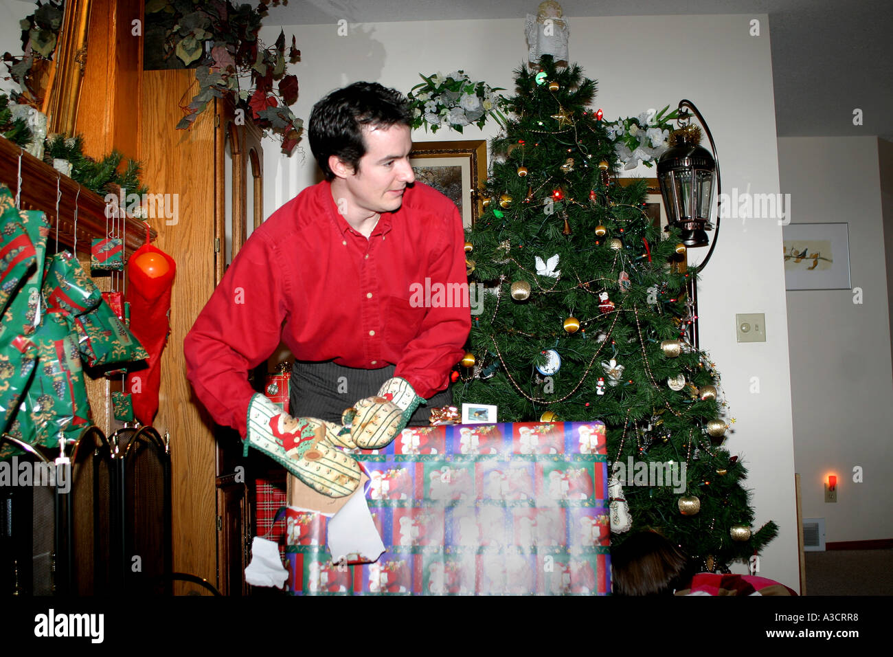 Thirty year old man wearing oven mitts opening his Christmas gifts ...