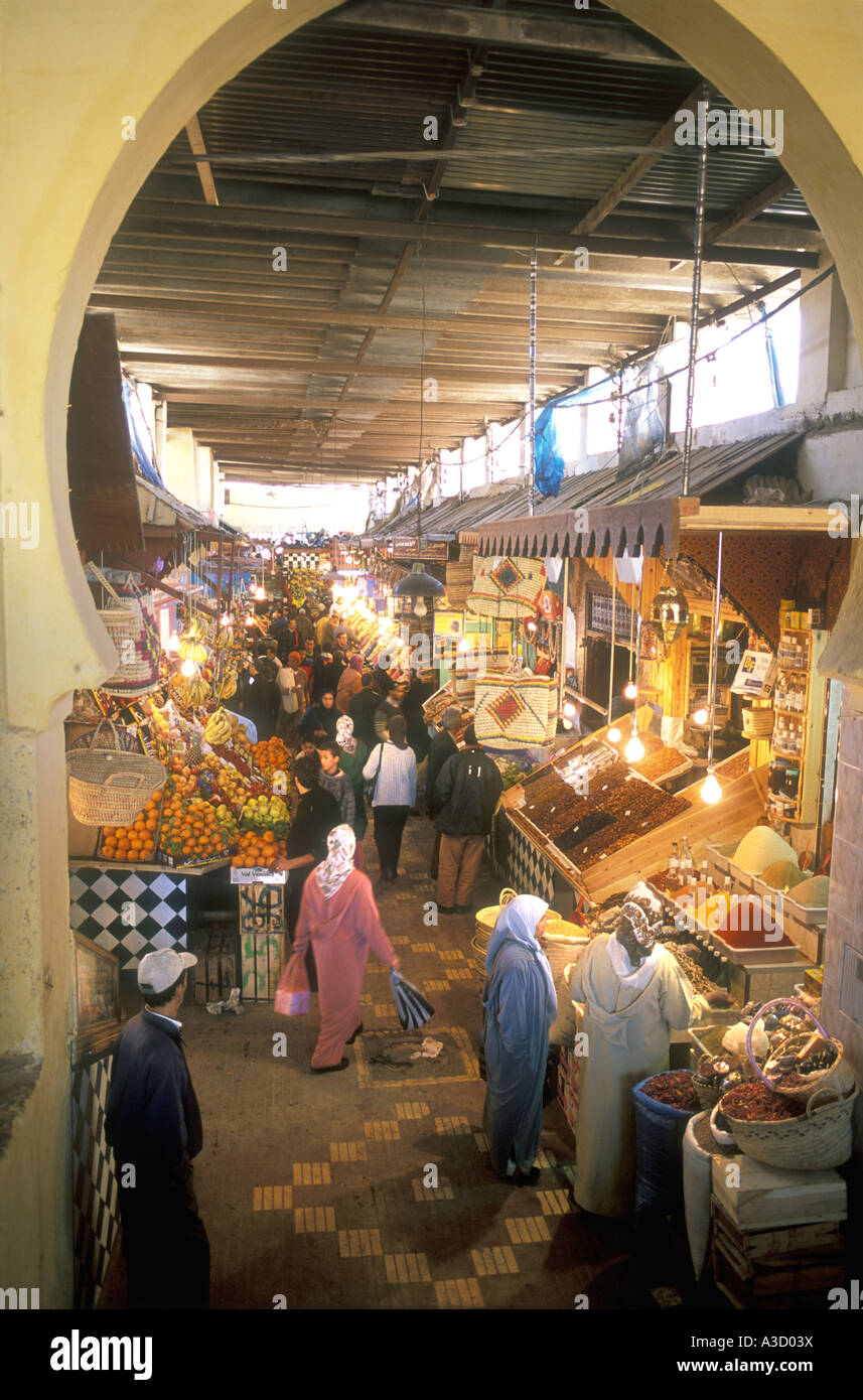Market shoppers buying food inside the busy souk in Fez Morocco - Stock Image