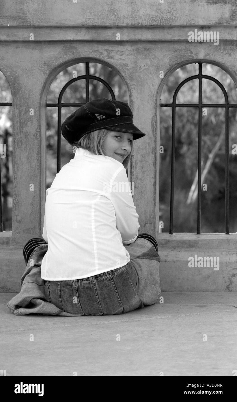 A young girl fasionably dressed, sitting down on a bridge - Stock Image
