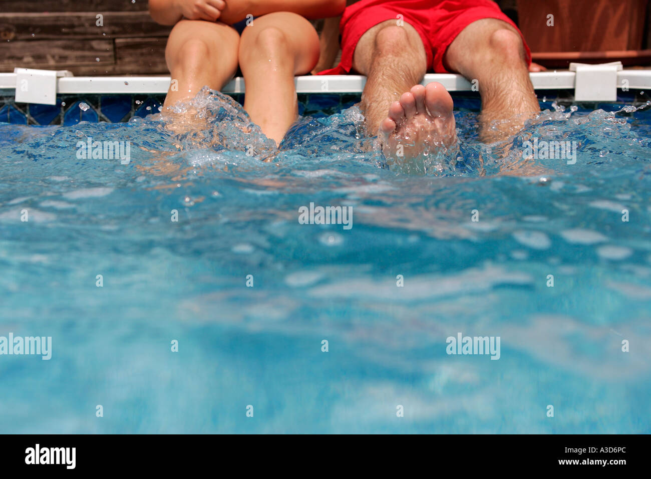 Young couple sitting by edge of swimming pool, focus on feet - Stock Image