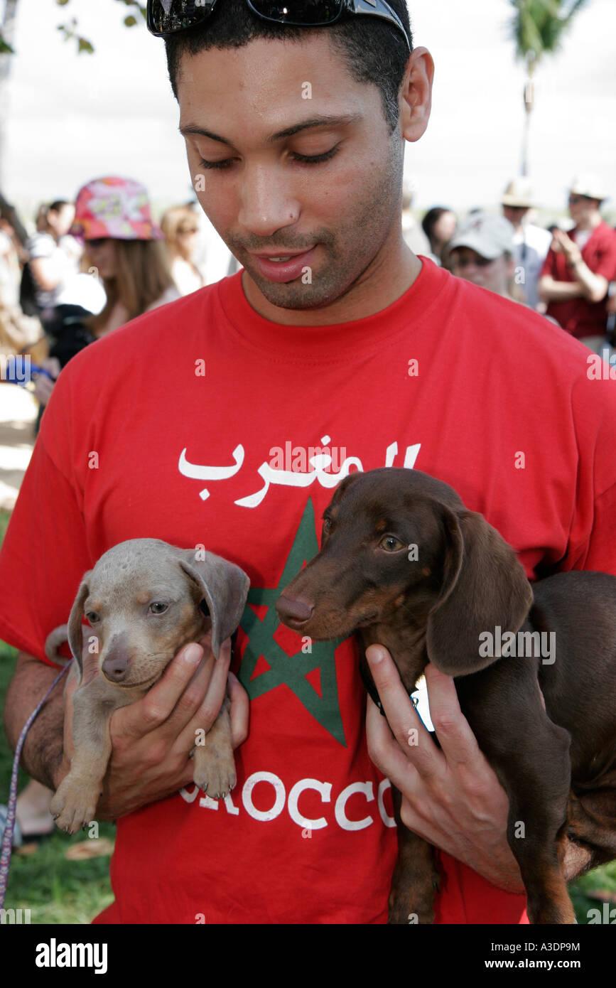 Miami Beach Florida Lummus Park South Beach Dachshund Winterfest dog pet owner Muslim man Morocco - Stock Image