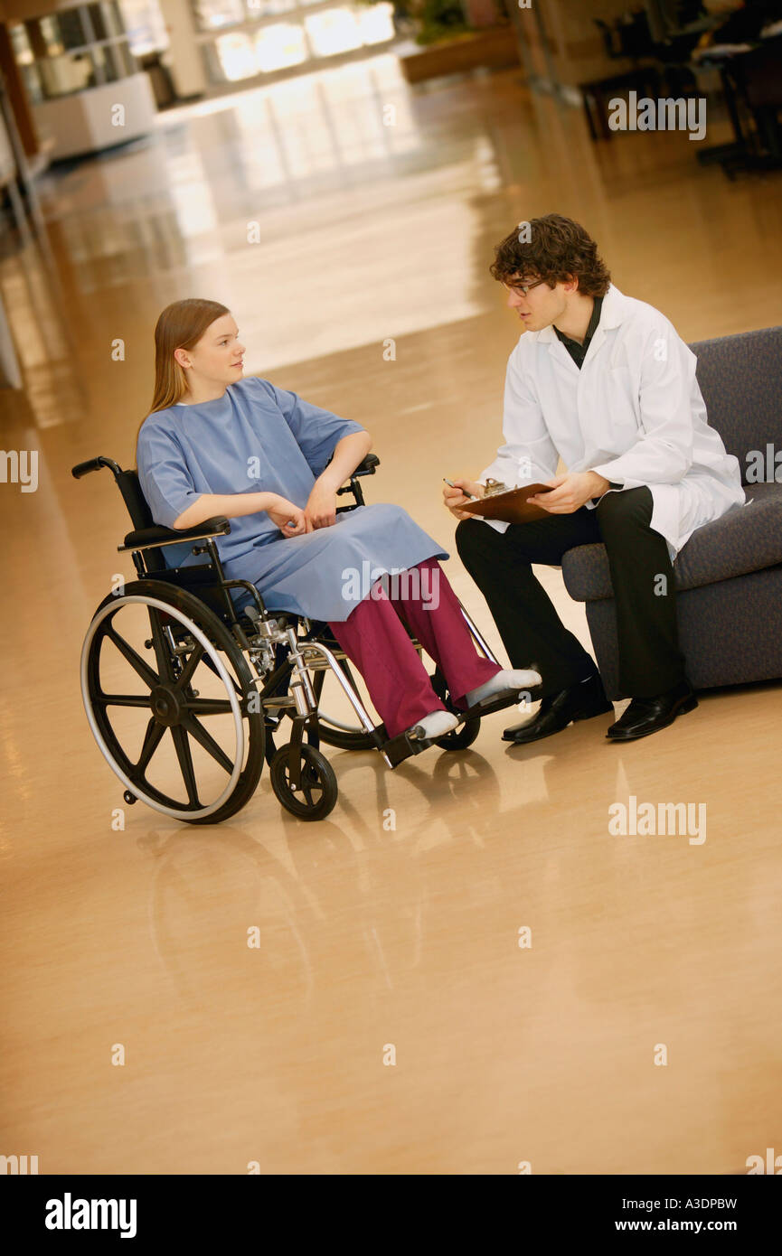 Young woman in wheelchair consulting with doctor - Stock Image