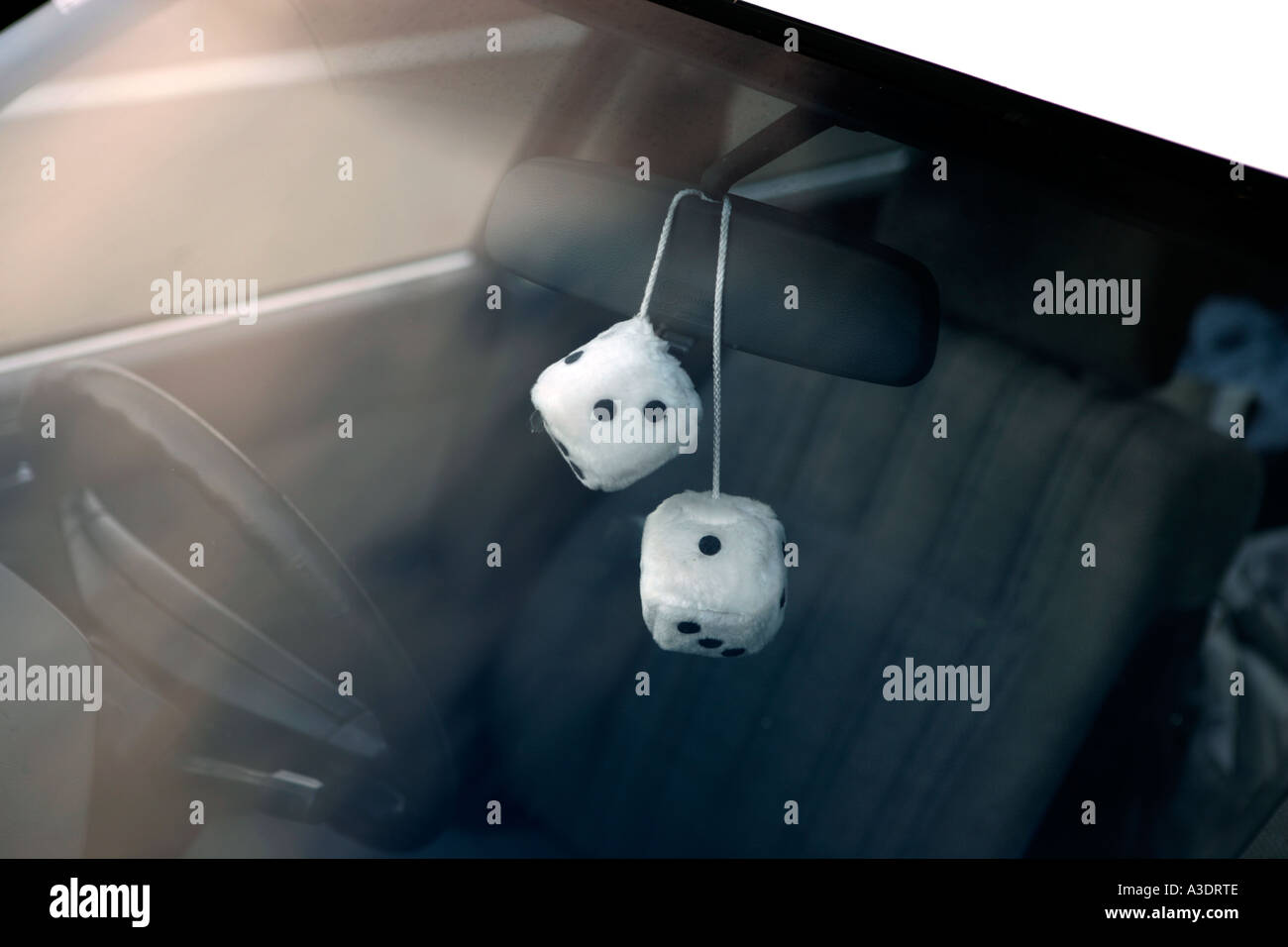 Two fluffy dice hanging on rear-view-mirror of a car, seen through windscreen - Stock Image
