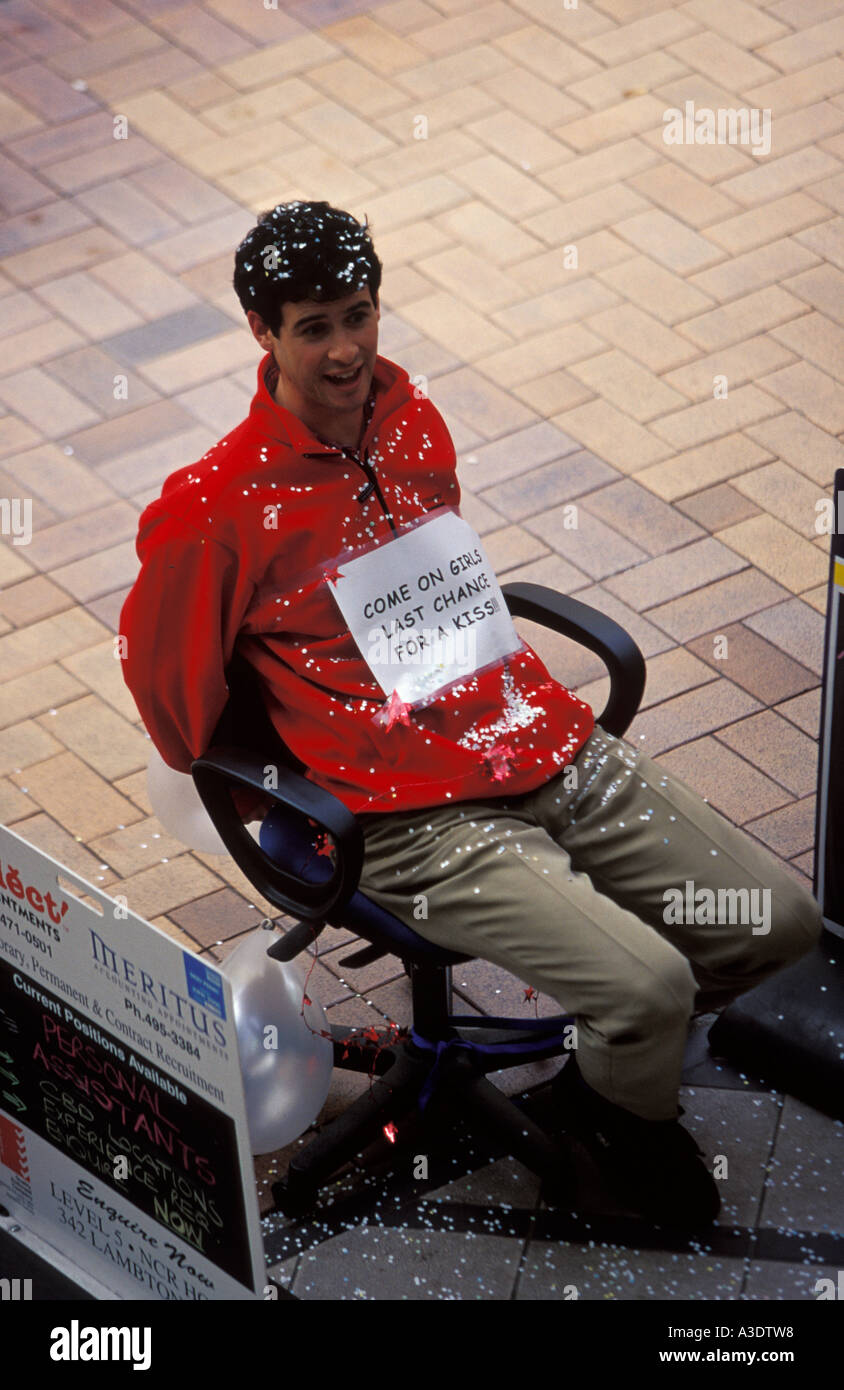 """Man tied to an office chair on pavement, with confetti, sign attached """"Come on girls, last chance for a kiss"""", New Stock Photo"""