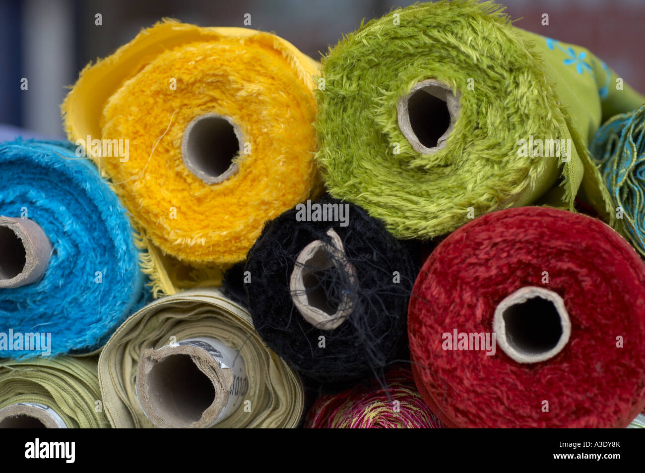 Colourful lengths of material for asian suits in fabric shop - Stock Image