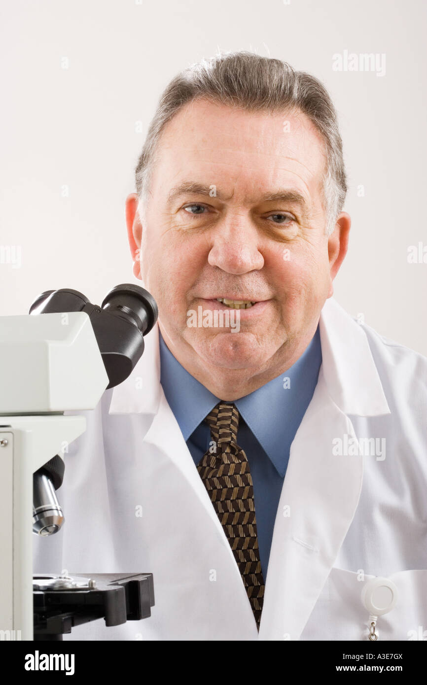 Researcher sits with his microscope, a powerful tool used to magnify research subjects or to make a diagnosis. - Stock Image