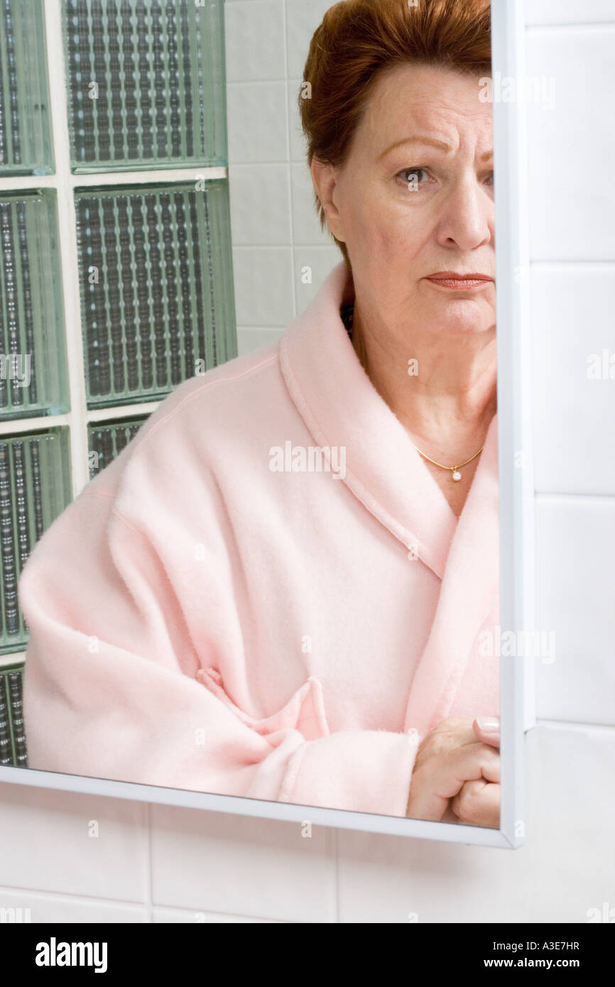 Woman looking concerned as she appears in her bathroom mirror. - Stock Image