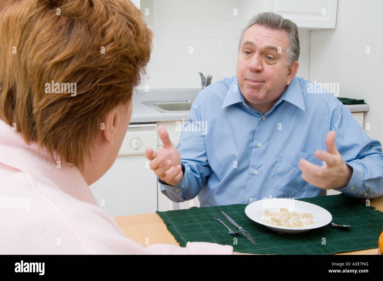 Senior couple having a spat or discussion in the kitchen. - Stock Image