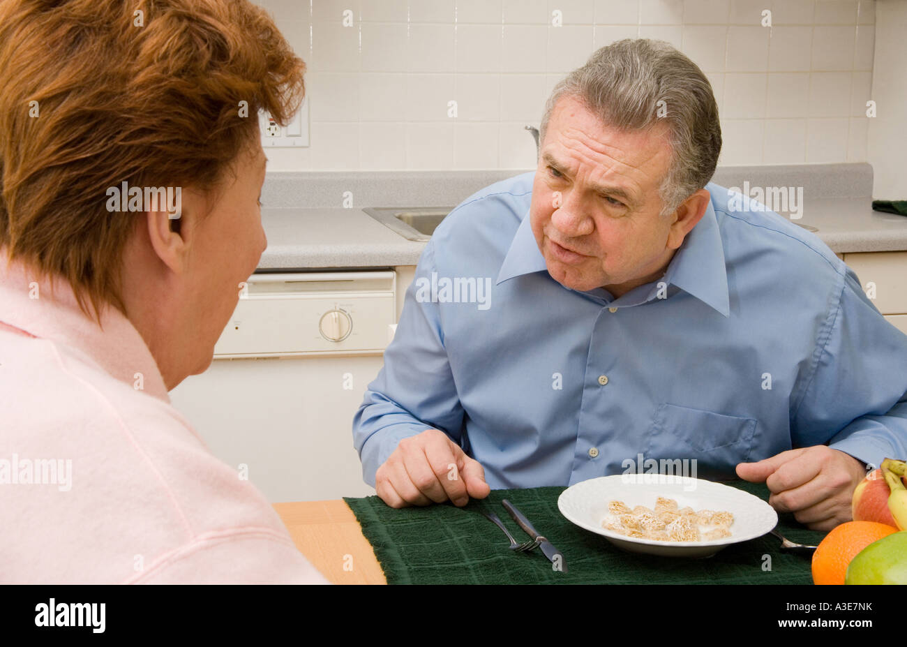 Senior married couple arguing during a meal. - Stock Image
