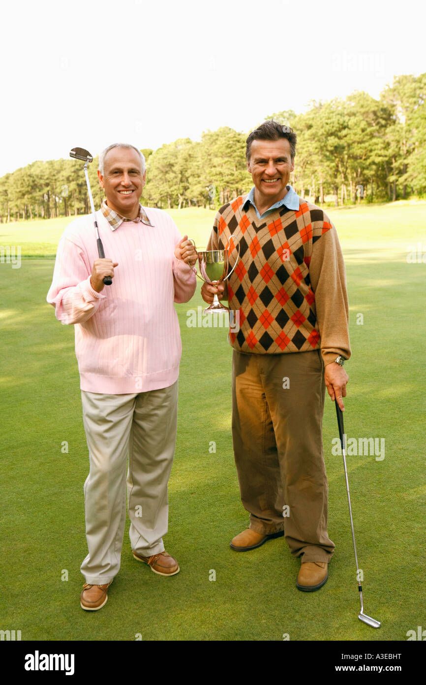 Portrait of two mature men holding a trophy and golf clubs - Stock Image