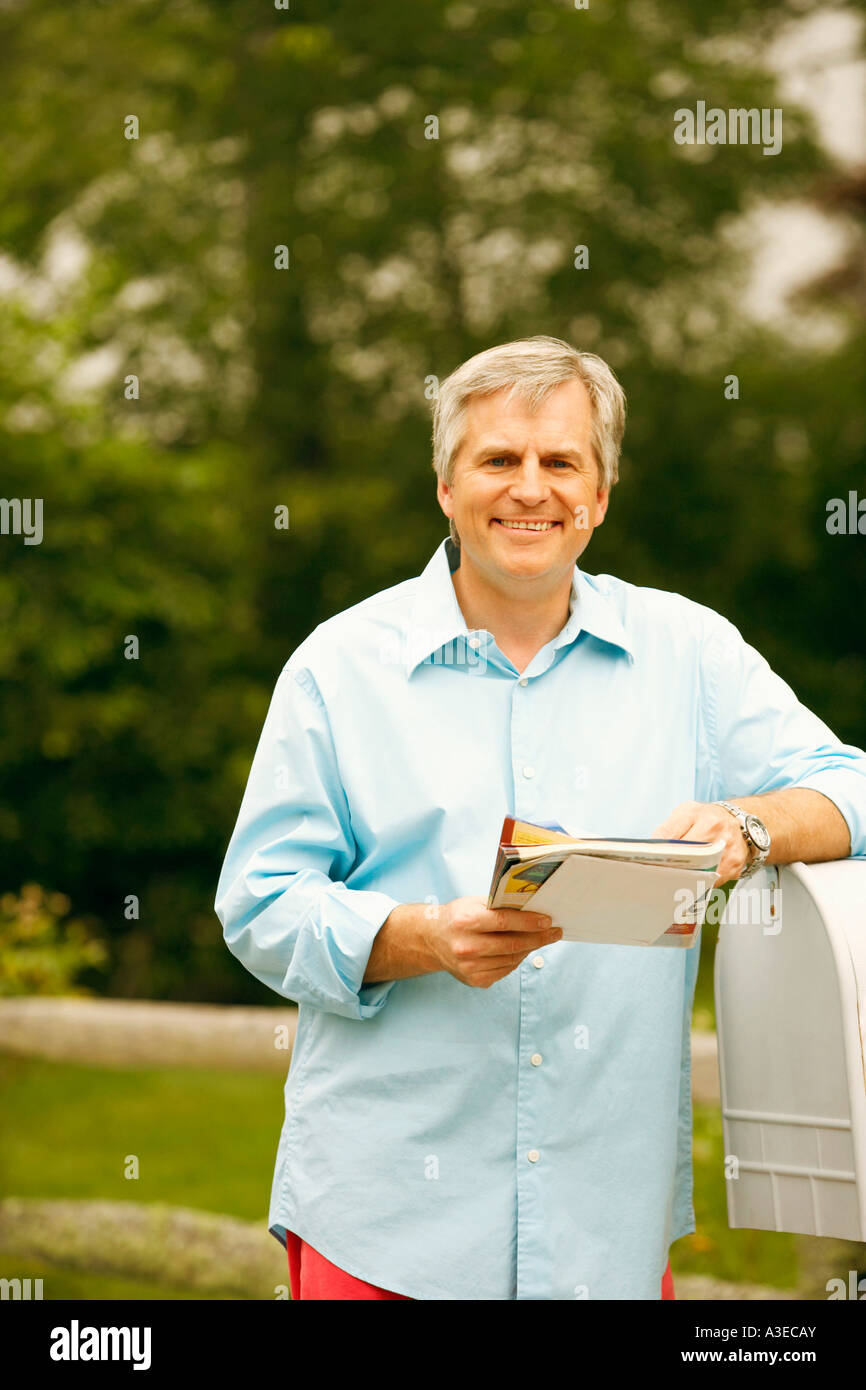 Portrait of a mature man standing beside a mailbox and holding mails - Stock Image
