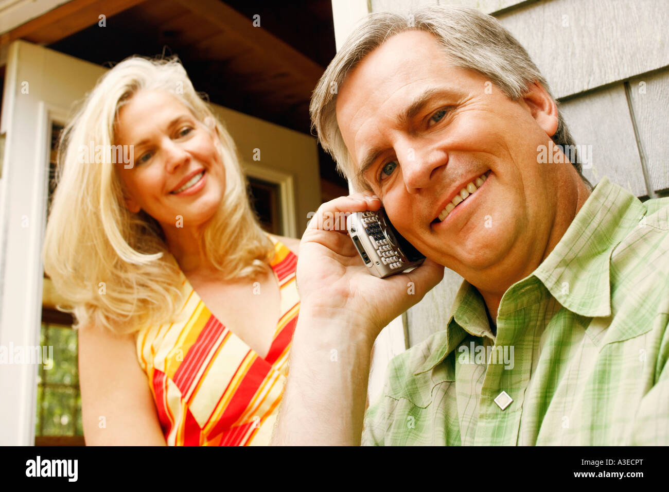 Low angle view of a mature man talking on a mobile phone with a mature woman smiling behind him - Stock Image