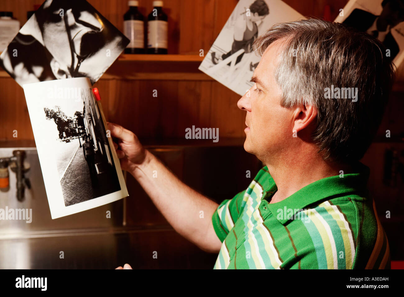 Side profile of a mature man looking at a photograph - Stock Image