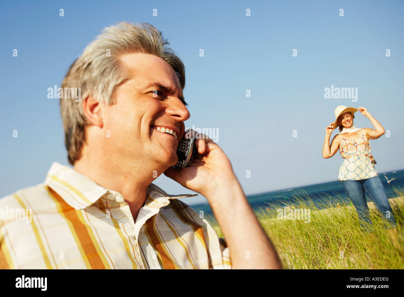 Close-up of a mature man talking on a mobile phone with a mature woman standing in the background - Stock Image