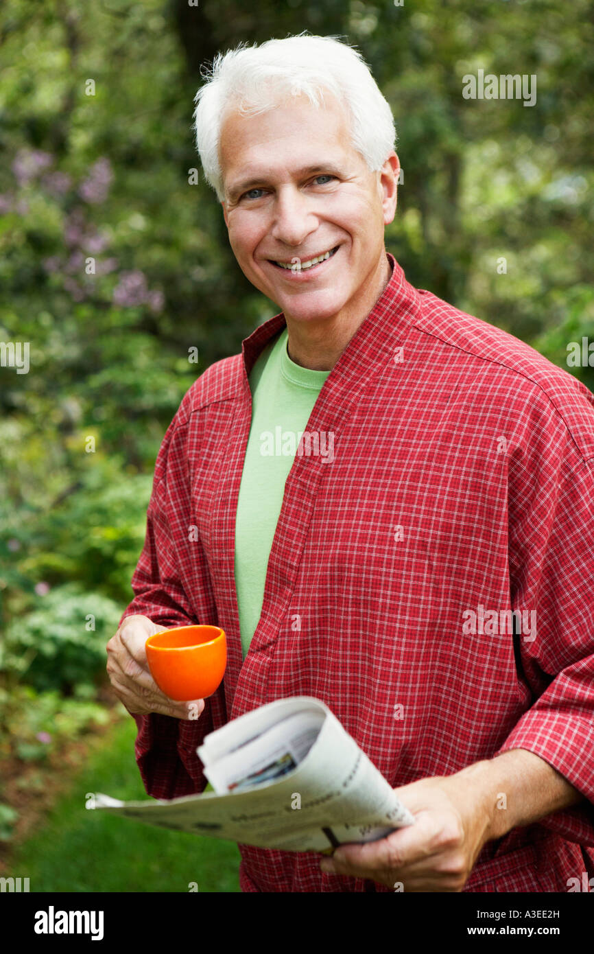 Portrait of a mature man holding a newspaper and a cup of tea - Stock Image