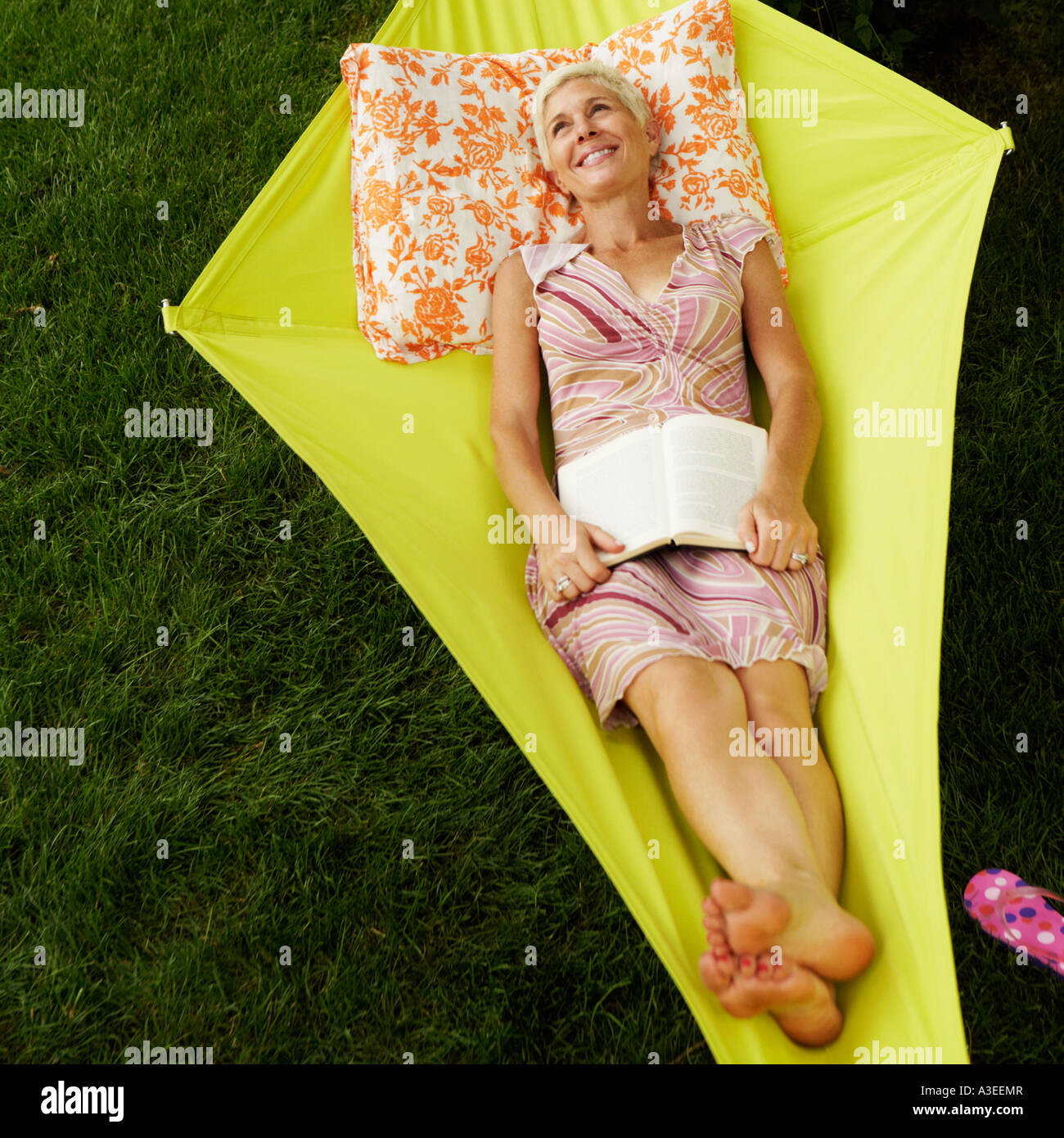 High angle view of a senior woman holding a book and lying in a hammock - Stock Image