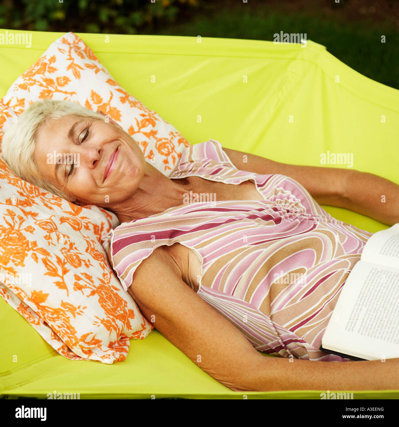 Side profile of a senior woman lying in a hammock with her eyes closed - Stock Image