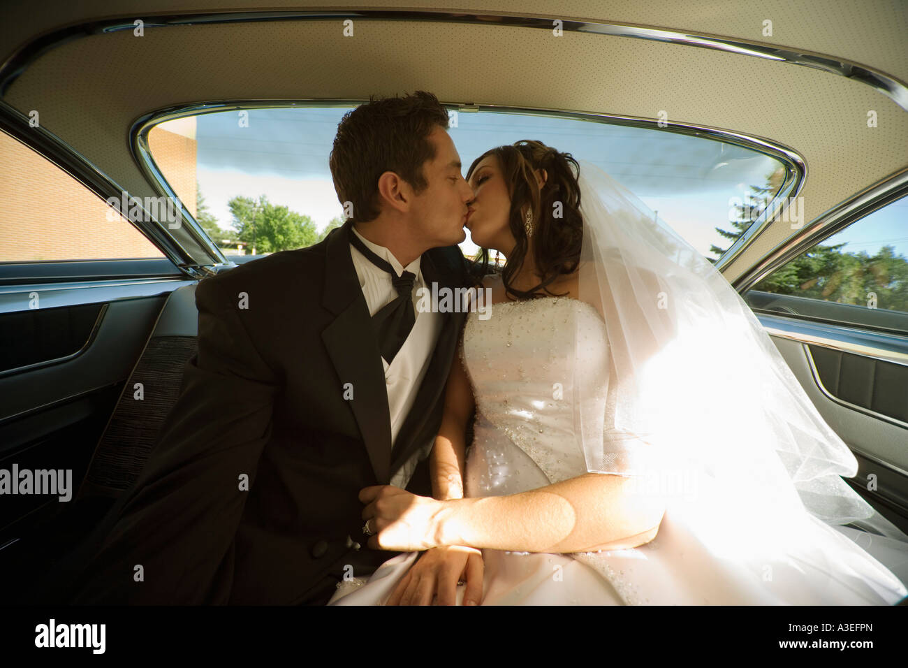 Bride and groom kissing in the backseat