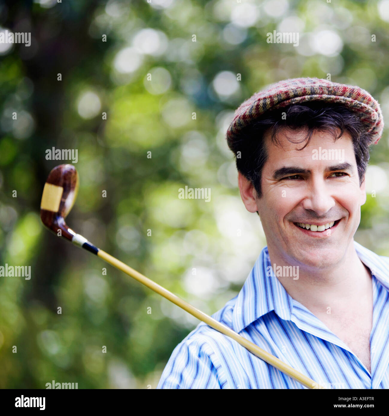 Close-up of a mature man with a golf club and smiling - Stock Image