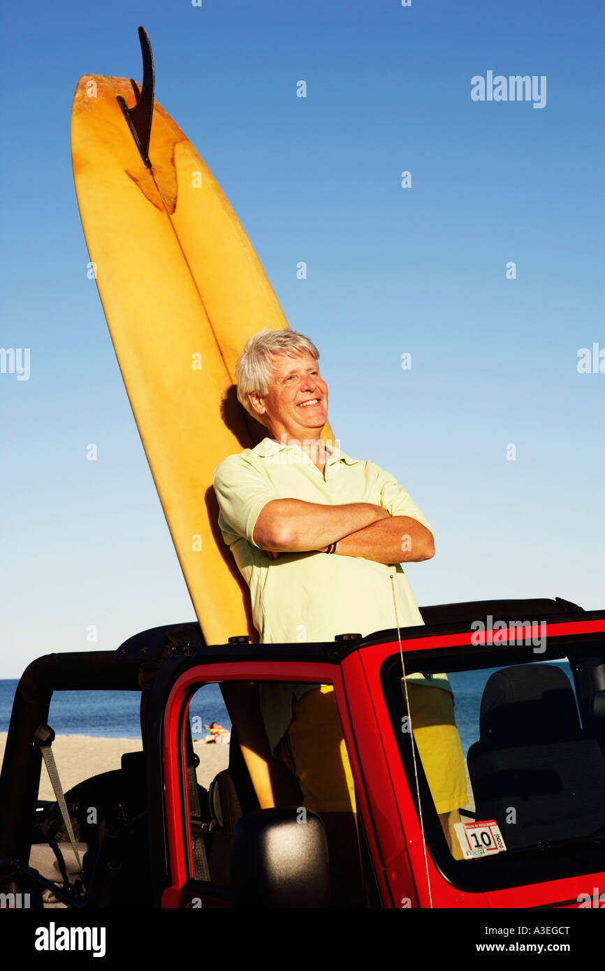 Mature man leaning against a surfboard in a sports utility vehicle - Stock Image
