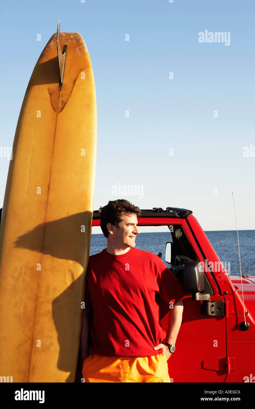 Mature man leaning against a sports utility vehicle with a surfboard - Stock Image
