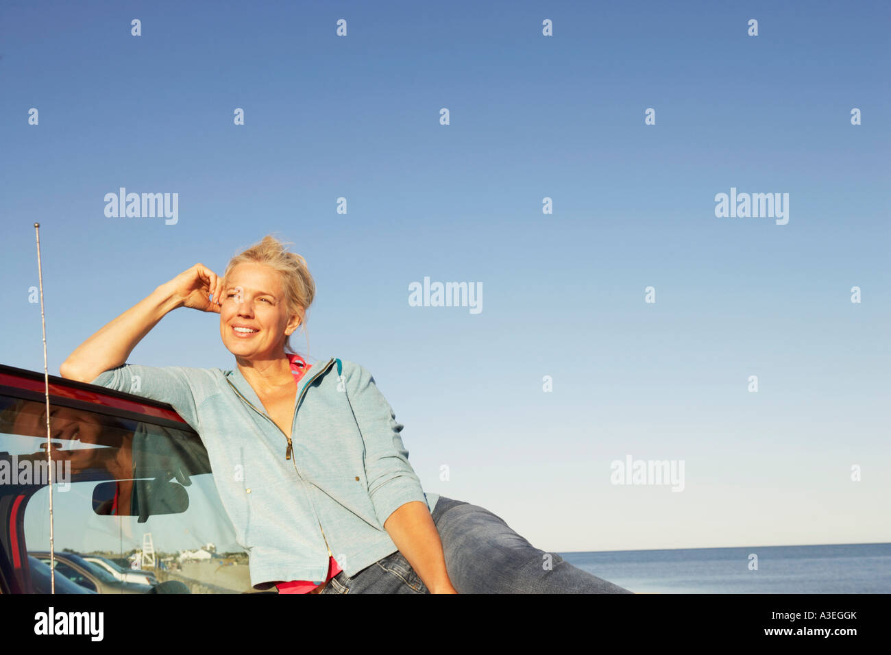 Mature woman sitting on the bonnet of a sports utility vehicle and looking away - Stock Image