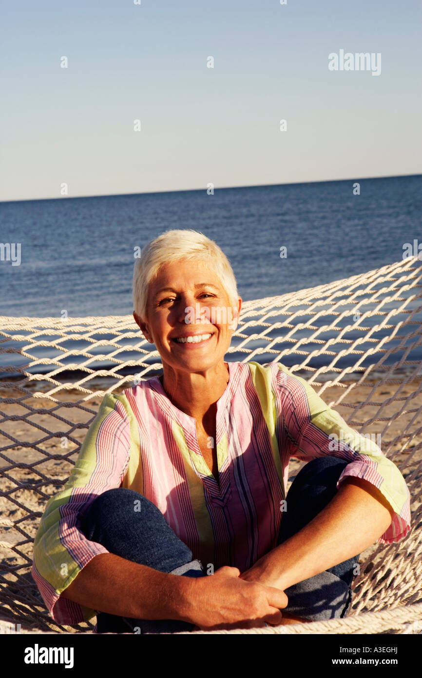 Portrait of a mature woman sitting in a hammock and smiling - Stock Image