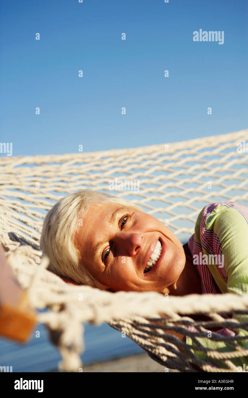 Portrait of a mature woman lying in a hammock and smiling - Stock Image