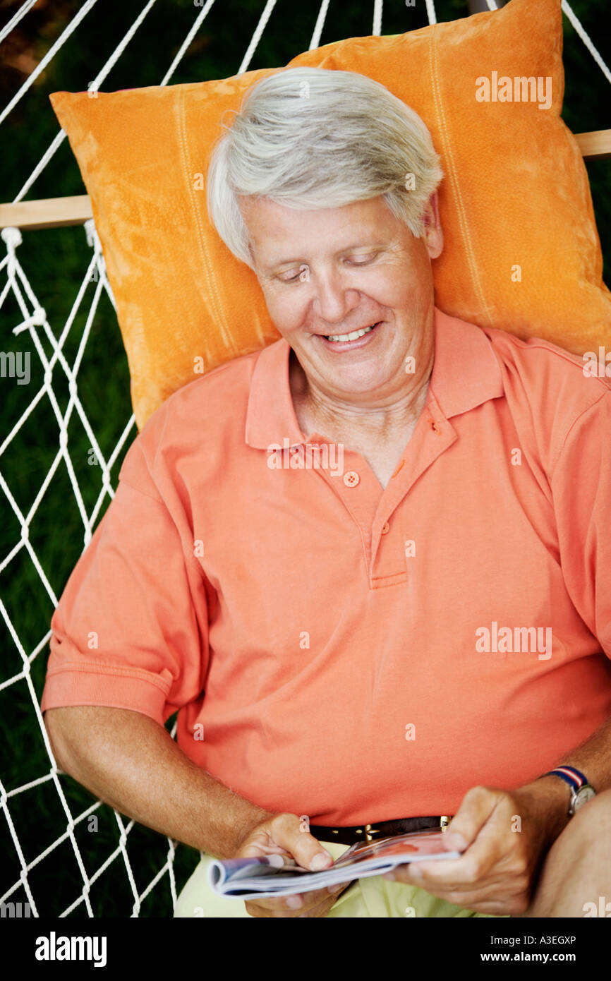 High angle view of a mature man lying in a hammock and reading a magazine - Stock Image