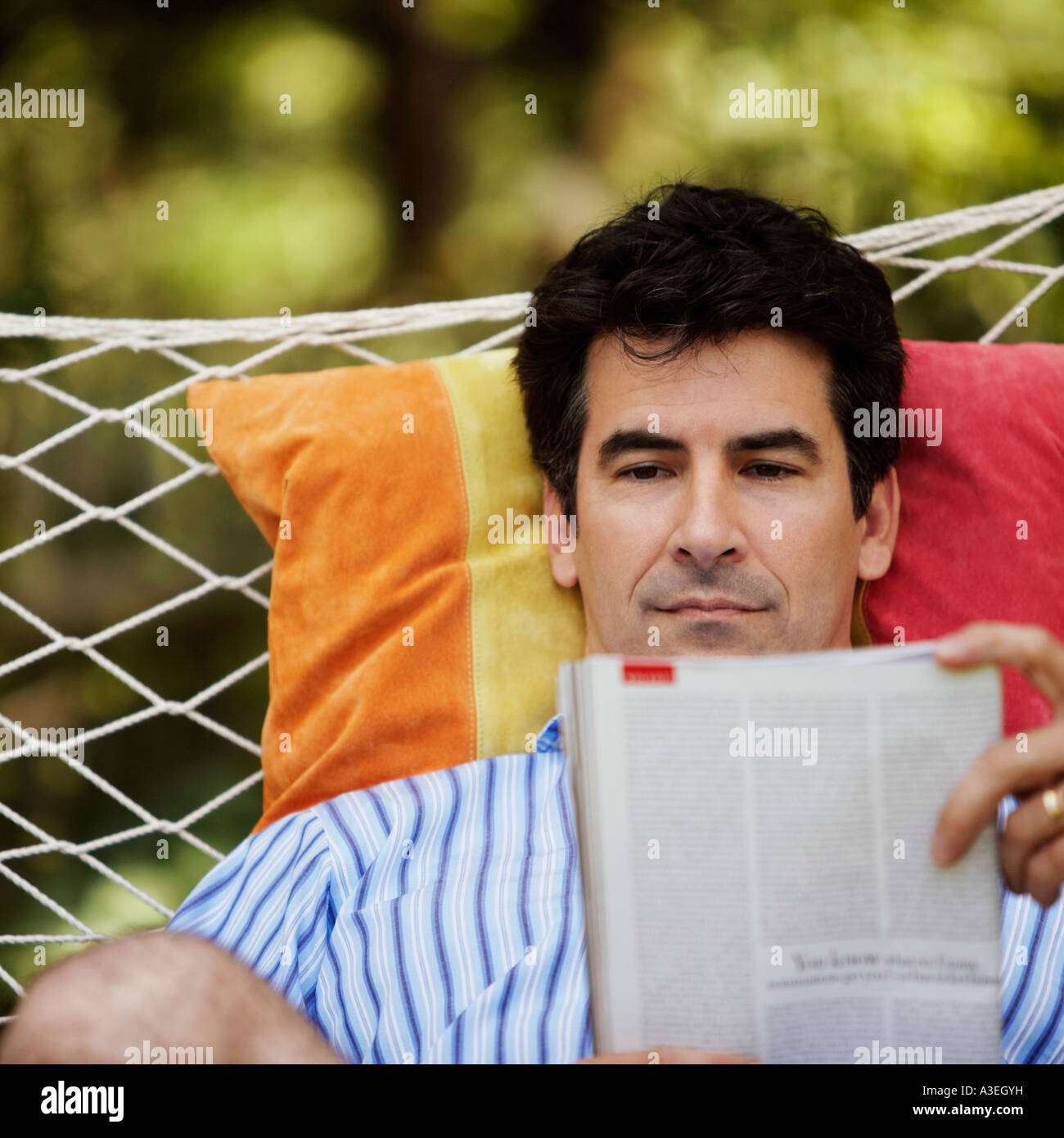 Close-up of a mature man lying in a hammock and reading a magazine - Stock Image