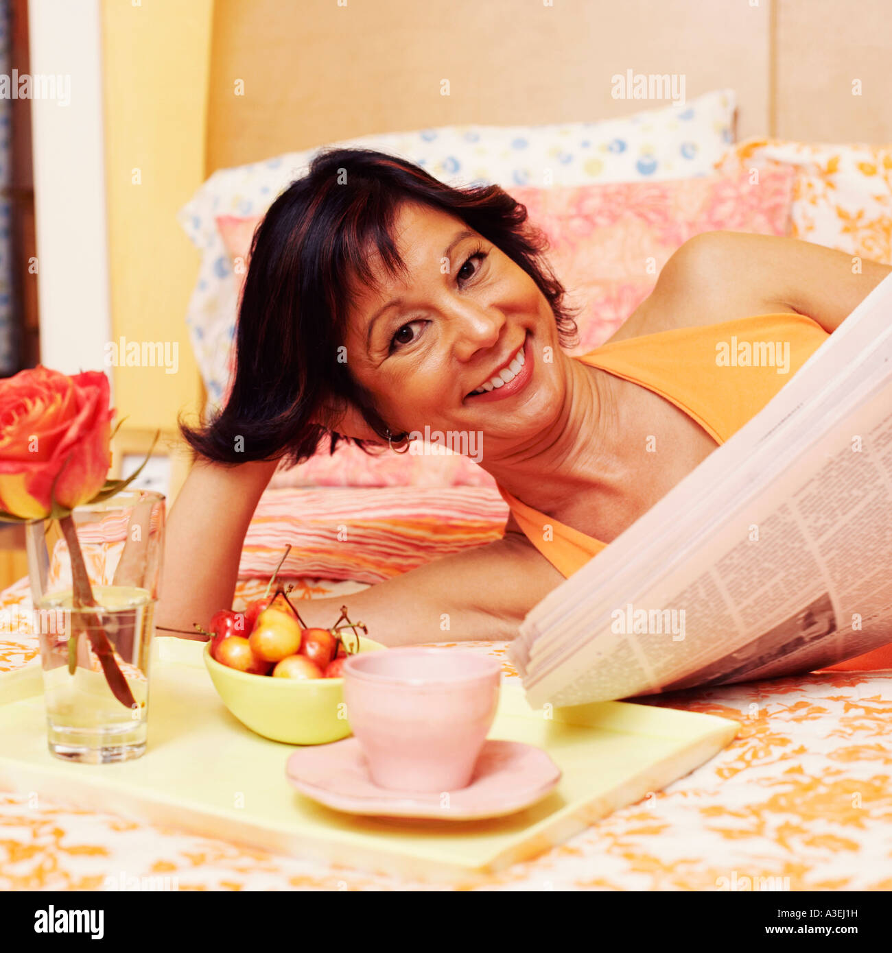 Portrait of a mature woman lying on the bed and holding a newspaper - Stock Image