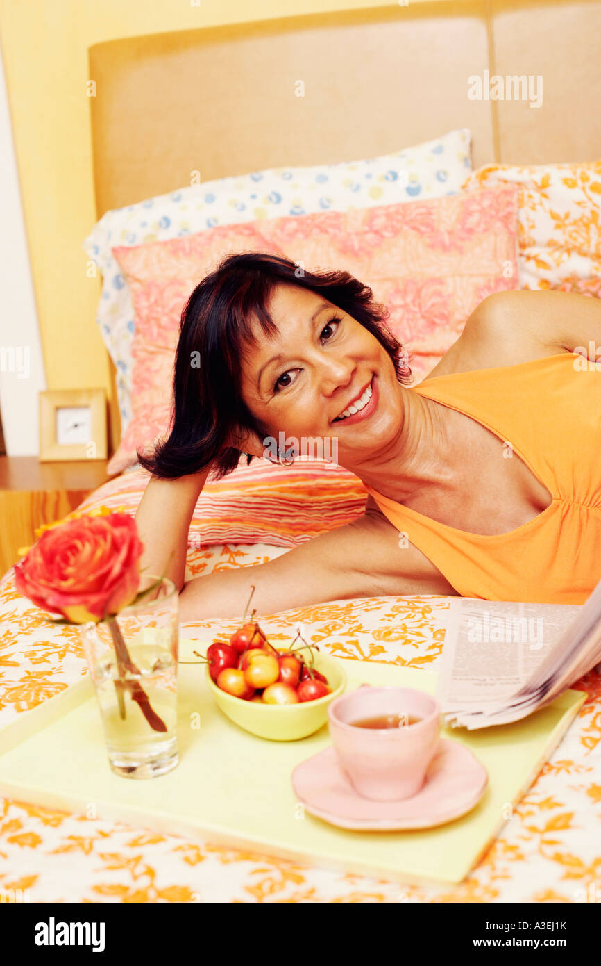 Portrait of a mature woman lying on the bed and smiling - Stock Image