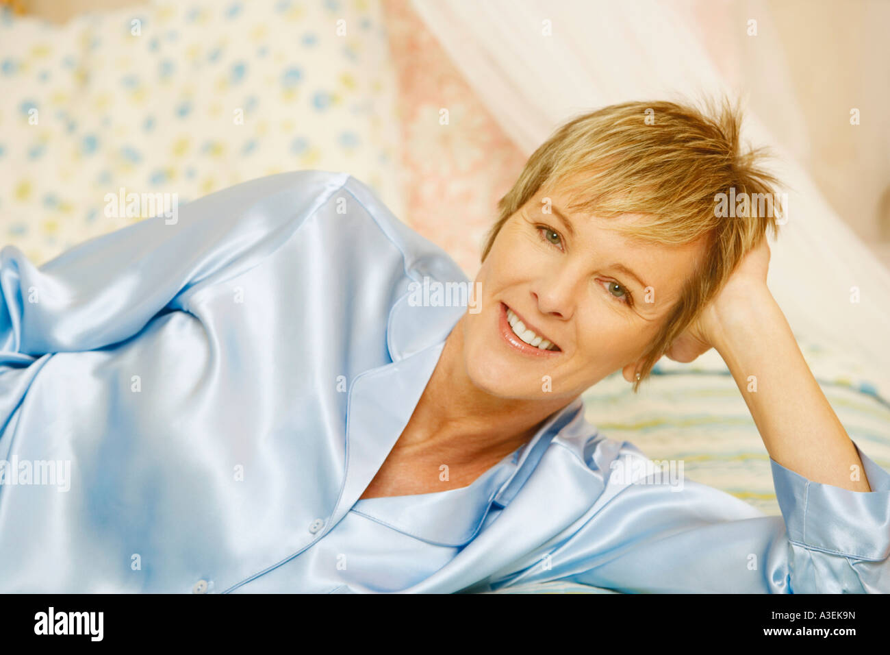 Portrait of a mature woman lying on the bed - Stock Image