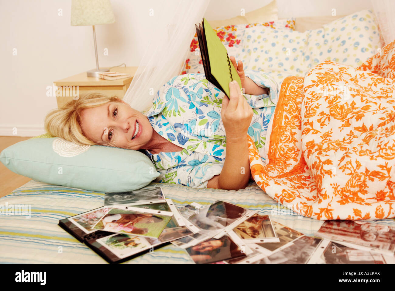 Mature woman lying on the bed and looking a photo album - Stock Image
