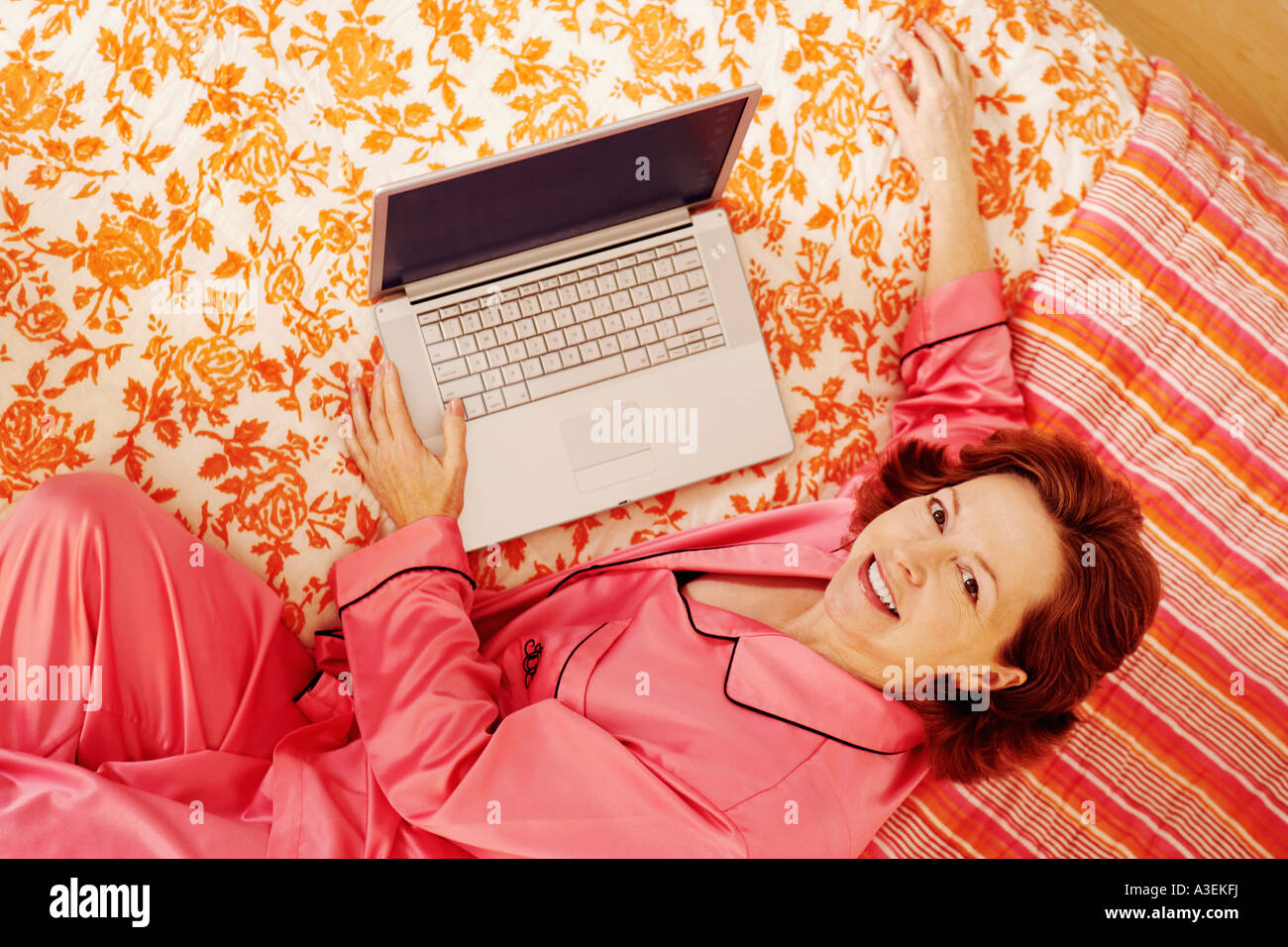Portrait of a mature woman lying in bed with a laptop and smiling - Stock Image