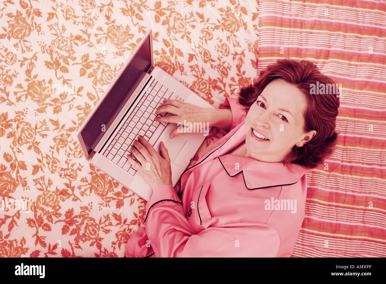 Portrait of a mature woman lying in bed and using a laptop - Stock Image