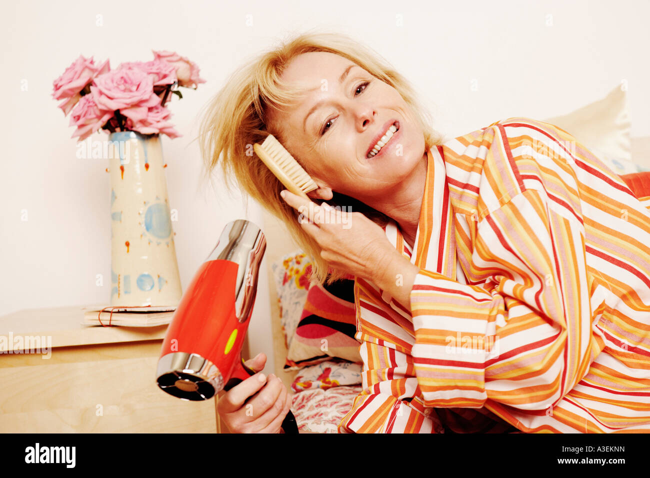 Portrait of a mature woman lying in bed and drying her hair with a hair dryer - Stock Image