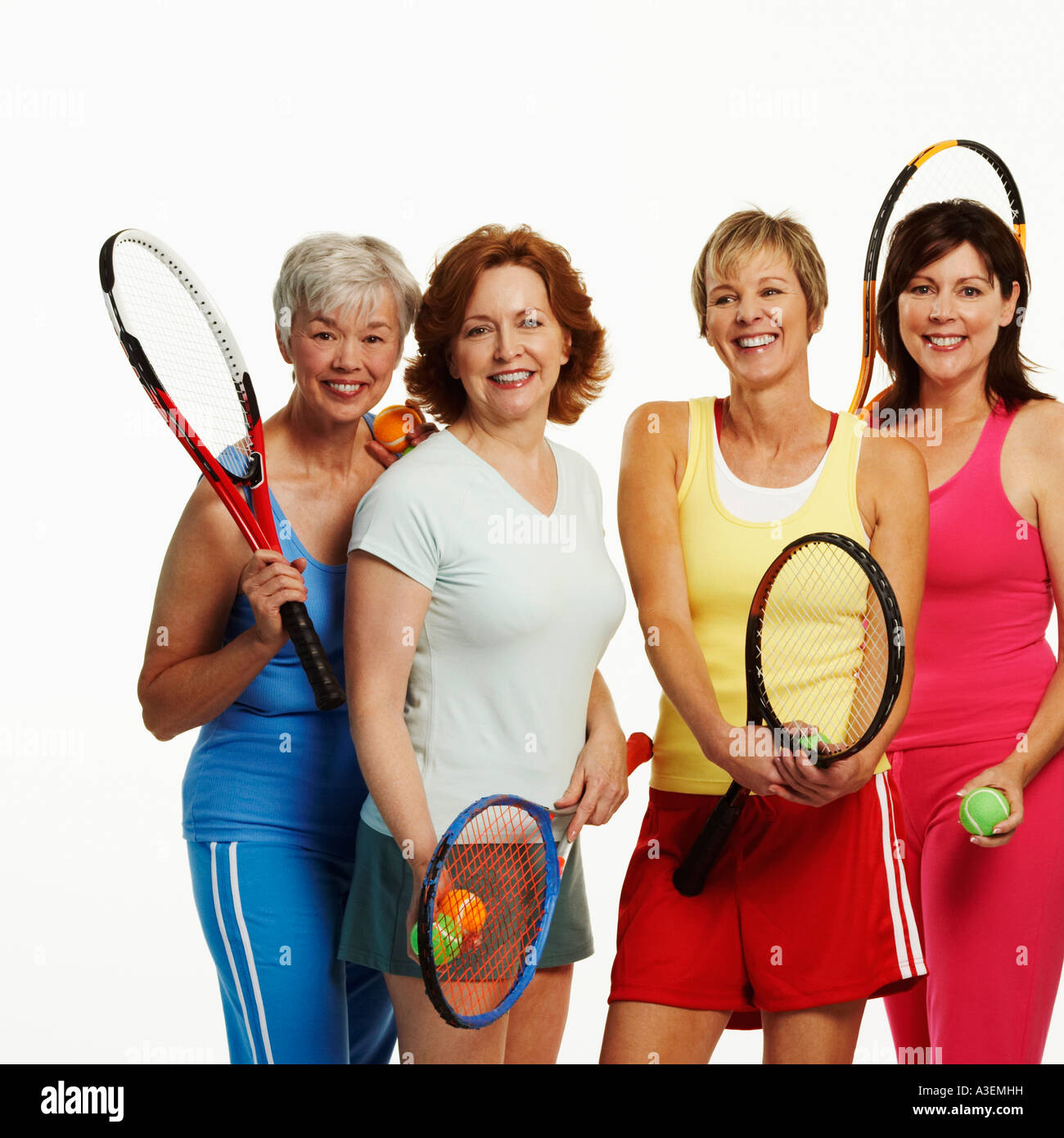 Portrait of four mature women holding tennis rackets and tennis balls Stock  Photo - Alamy