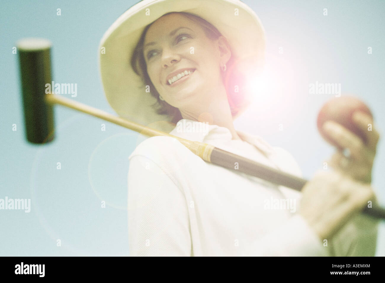 Low angle view of a mid adult woman holding a croquet mallet and a ball Stock Photo