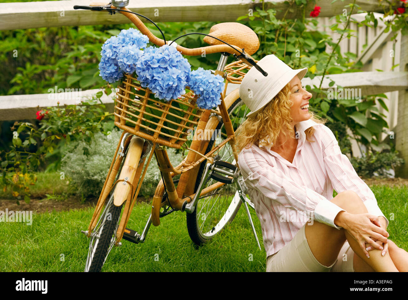 Mature woman sitting beside a bicycle - Stock Image
