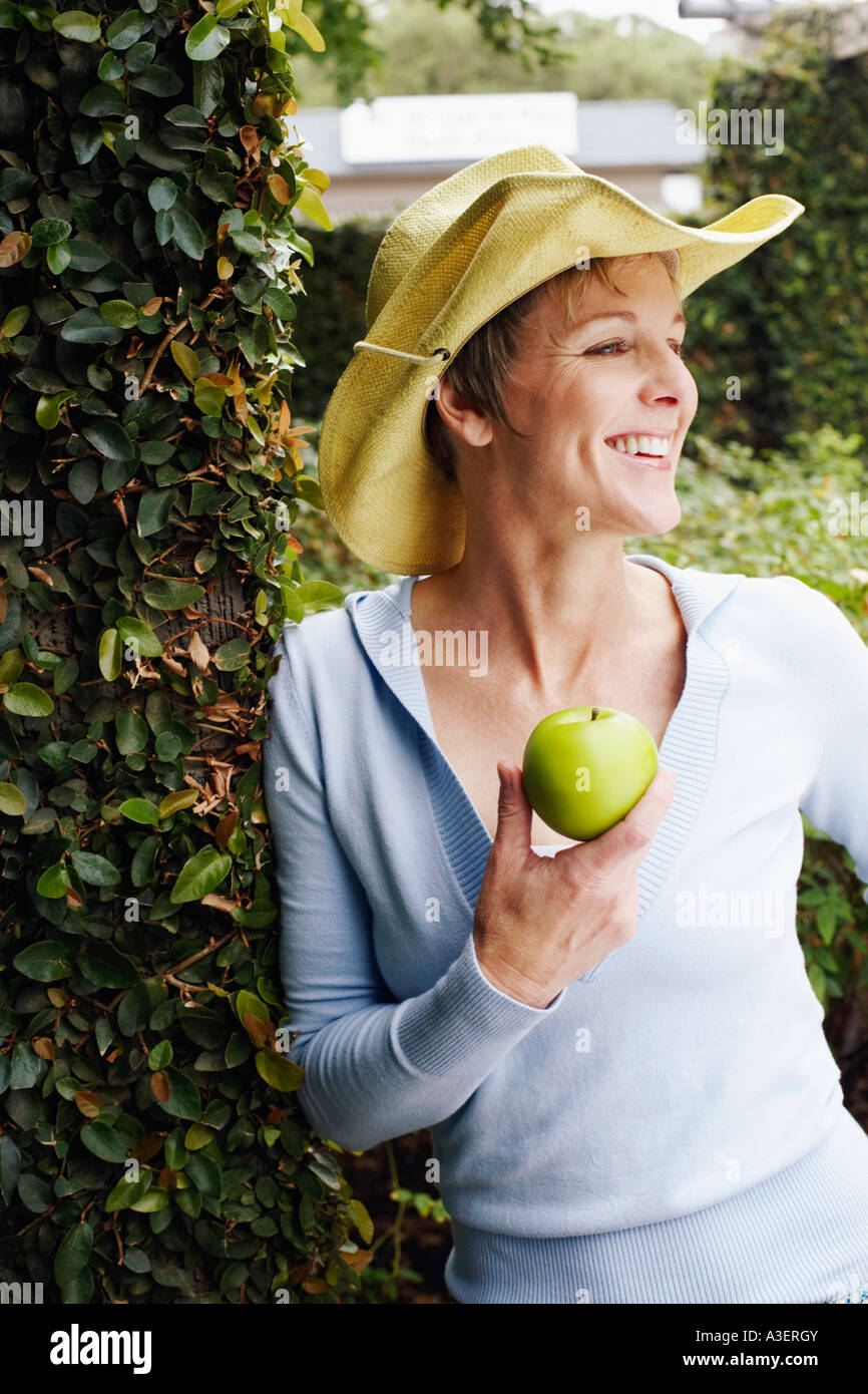 Close-up of a mature woman holding a granny smith apple - Stock Image