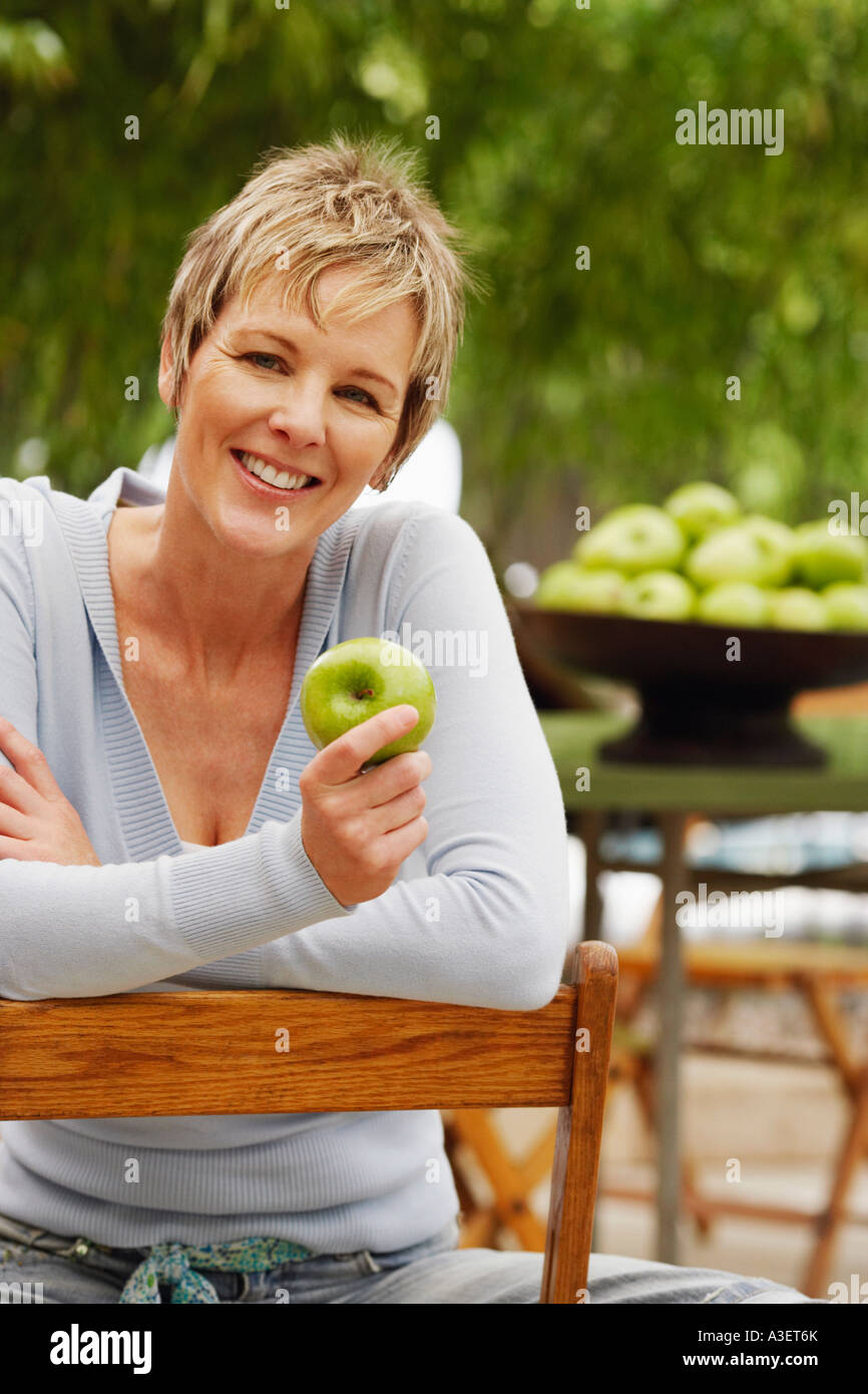 Portrait of a mature woman holding a granny smith apple and smiling - Stock Image