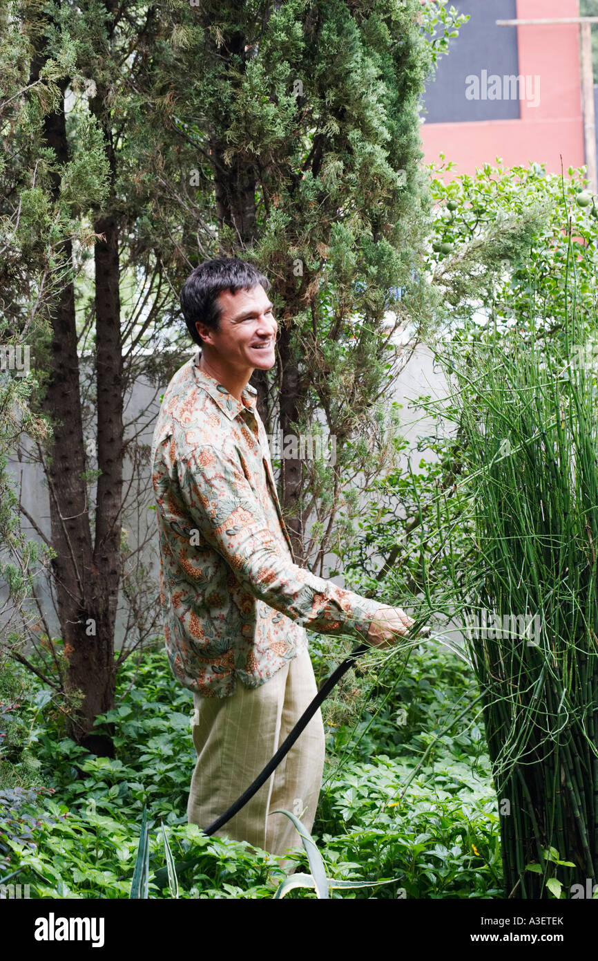 Side profile of a mature man watering plants in the back yard - Stock Image