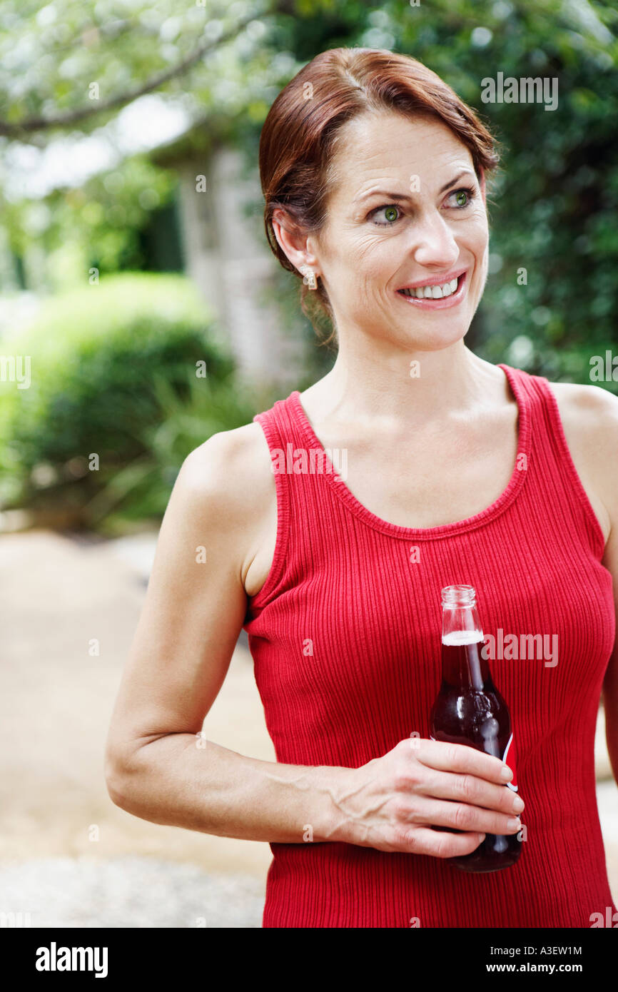 Close-up of a mature woman holding a bottle of wine and smiling - Stock Image