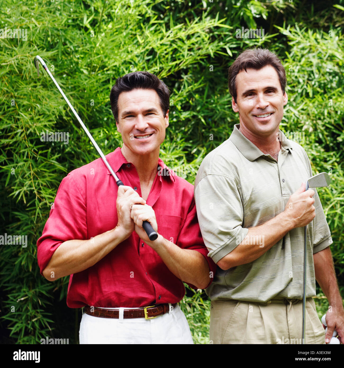 Two mature men holding golf clubs and smiling - Stock Image