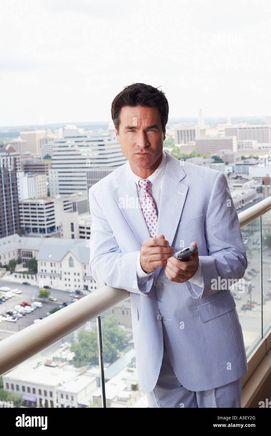 Portrait of a businessman using a personal data assistant - Stock Image