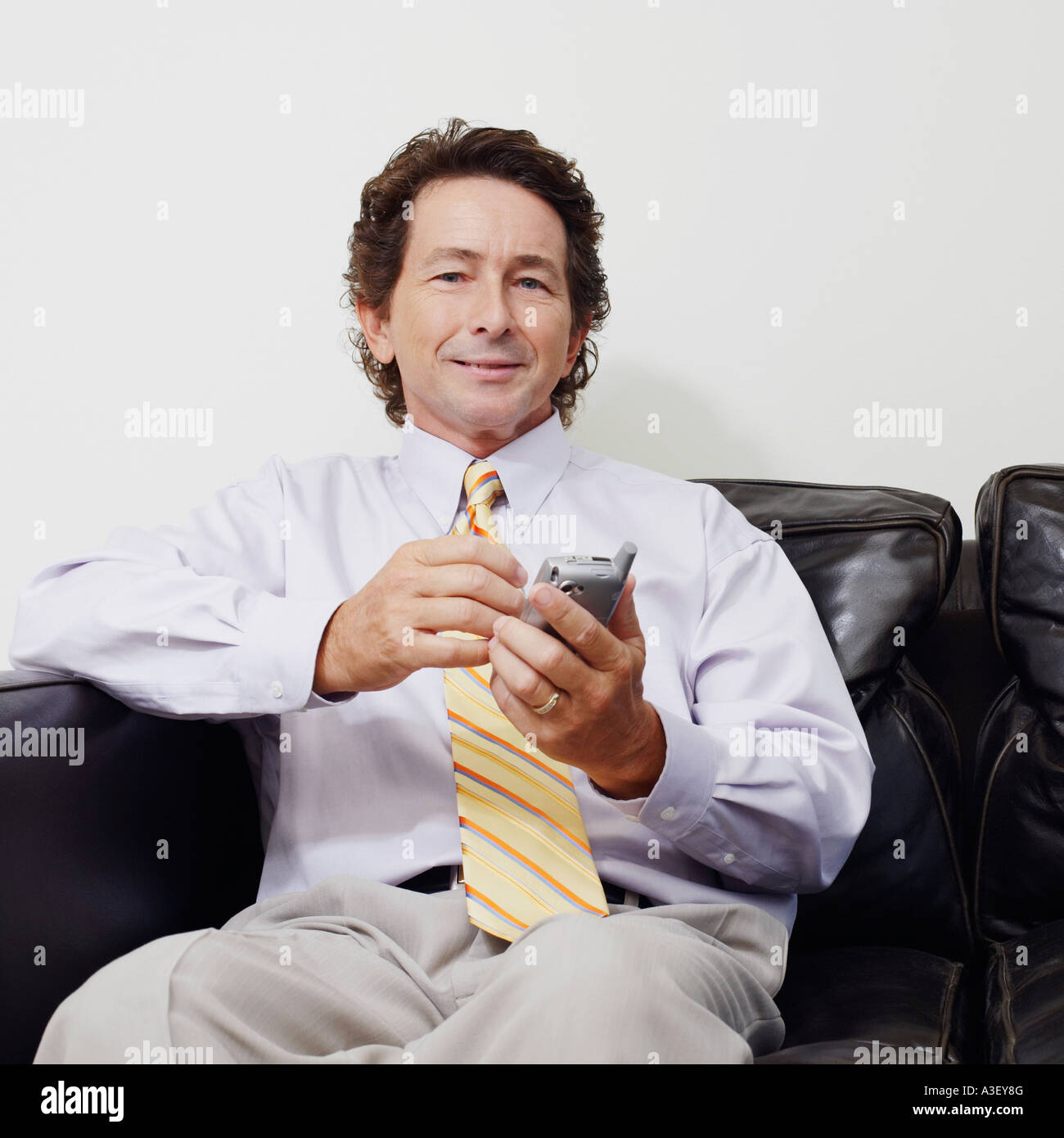 Portrait of a businessman sitting on a couch and holding a mobile phone - Stock Image